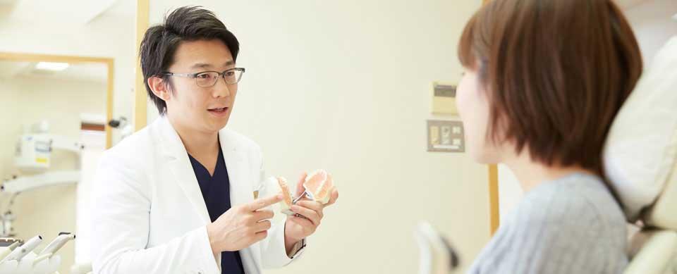 歯の模型を用い治療方法を説明してる髙田孝俊院長
