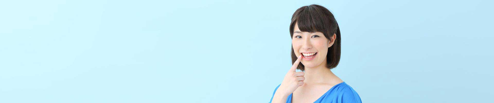 歯を指さす女性