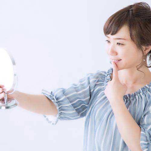 鏡で歯をみる女性